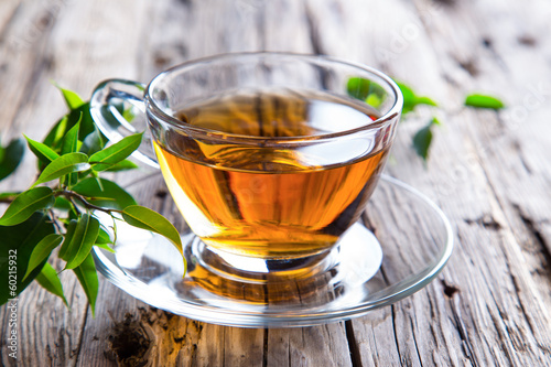 Poster Thee Transparent cup of green tea on wooden background