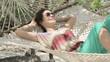 Young happy woman lying, relaxing on hammock