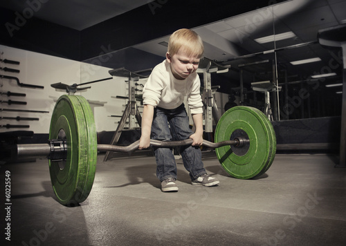 Fotografia  Determined young boy trying to lift a heavy weight bar