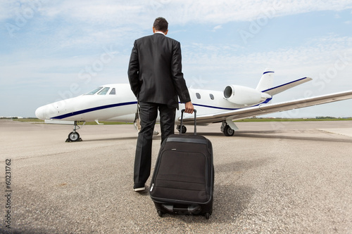 Fototapeta Businessman Walking Towards Corporate Jet obraz
