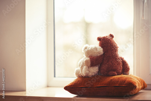 Fotografía Two embracing teddy bear toys sitting on window-sill