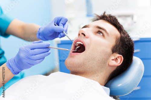 Man having teeth examined at dentists плакат