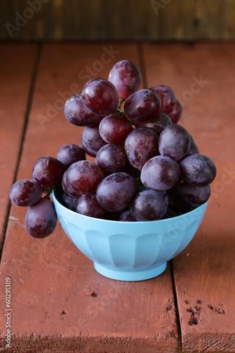 Valokuvatapetti large ripe black grapes in a blue bowl