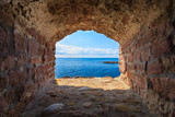 Fototapeta Przestrzenne - Blue sea seascape from hole window frame in old stone wall