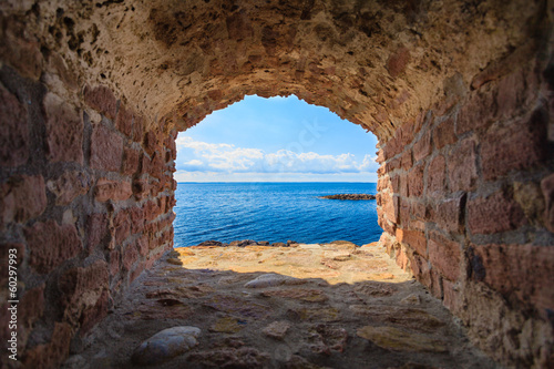 Blue sea seascape from hole window frame in old stone wall