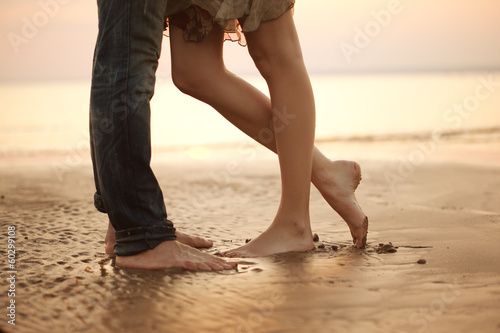 A loving young couple hugging and kissing on the beach. Lovers m Fototapeta