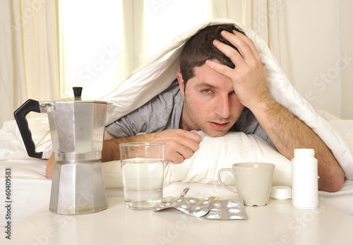 Fotografie, Obraz  Man with headache and hangover in bed with tablets