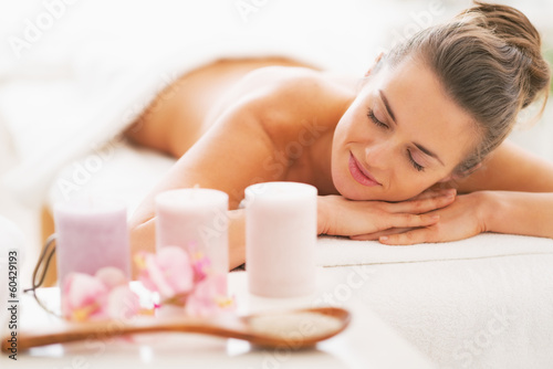 Closeup on spa therapy ingredients and woman in background