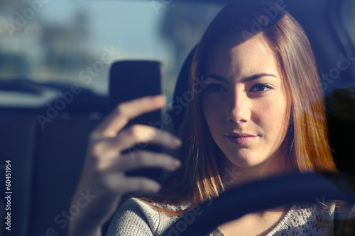 Fotografia, Obraz  Front view of a woman driving a car and typing on a smart phone