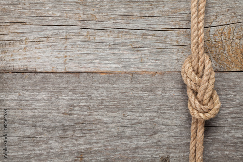 Obraz Ship rope knot on wooden texture background - fototapety do salonu