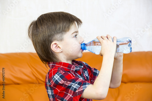 Fototapeta boy drinks water from a plastic bottle obraz na płótnie