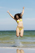 Beautiful summer woman in swimsuit jumping over seaside.