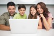 Portrait of a smiling couple with kids using laptop