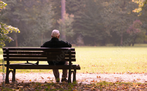 Fotografía  Old man sitting on a bench in autumn, autumn of life