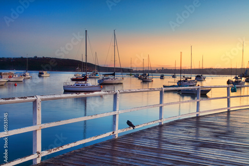 Boats moored bobbing in the waters at sunrise