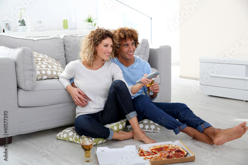 Valokuva Cheerful couple at home having pizza in font of TV