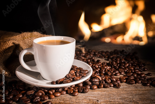 Door stickers Cafe Cup of hot coffee and coffee beans near fireplace