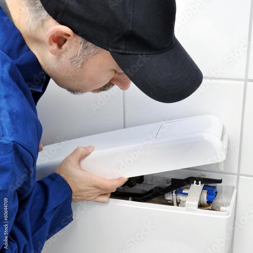 Fotografia  Sanitär-Installateur repariert WC-Spülkasten