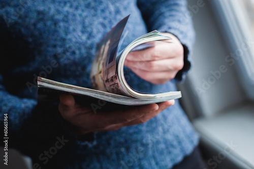 Photographie  Un homme regarde un magazine. Appuyez sur les mains.