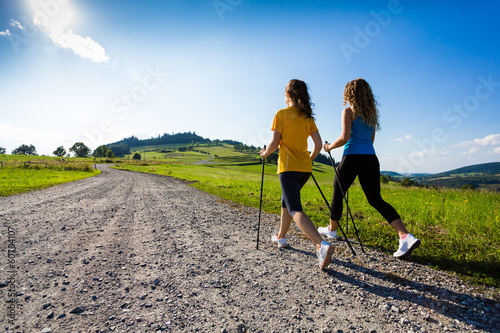 Foto  Nordic walking - active people working out outdoor