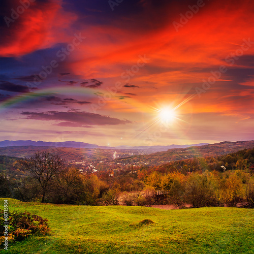 Foto op Aluminium Rood village on hillside meadow with forest in mountain at sunset