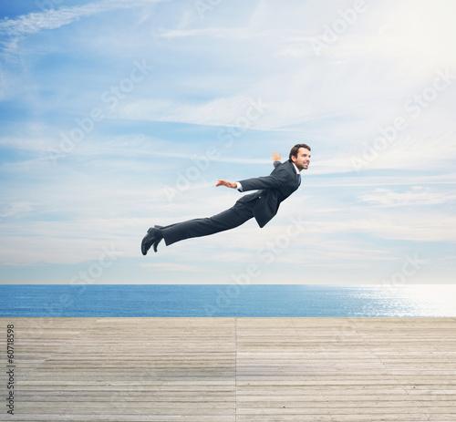 Man in suit flying over boardwalk Poster Mural XXL