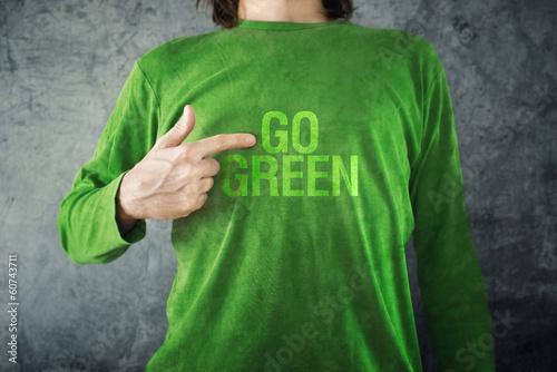 Valokuva  Go green. Man pointing to title printed on his shirt