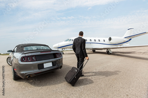 Fotografia Businessman Standing By Car And Private Jet At Terminal