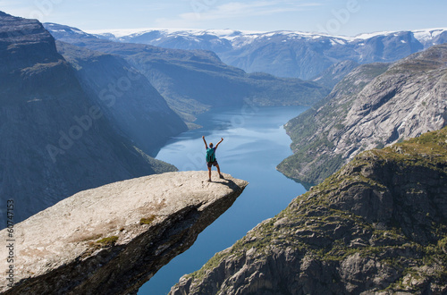 Poster Scandinavië girl with backpack on trolltunga in norway