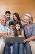 Extended family using laptop on sofa in living room