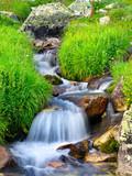 Wodospad wśród trawy i kamieni. - 60759526