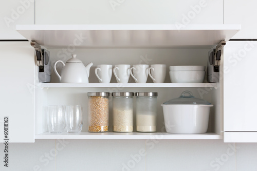 opened cupboard with kitchenware inside Canvas Print