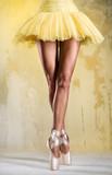 Ballerina on point over obsolete wall