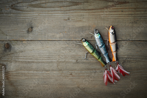 Poster Fishing colorful lures on the wooden pier