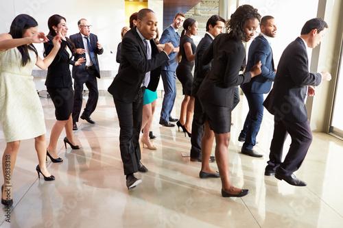 Foto auf Gartenposter Tanzschule Businessmen And Businesswomen Dancing In Office Lobby