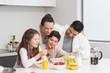 Happy kids enjoying breakfast with parents in kitchen