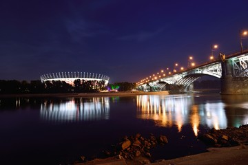 Panel SzklanyPoniatowski Bridge and National Stadium in Warsaw by night.