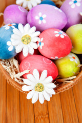 Obraz na płótnie Canvas Easter eggs decorated with daisies tucked in a basket