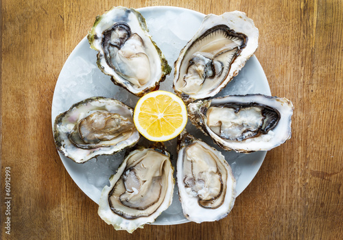 Fresh oysters in a white plate with ice and lemon Slika na platnu