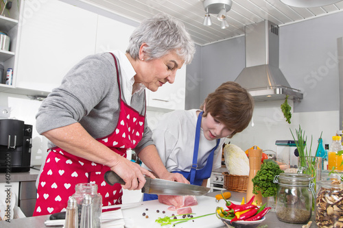 Foto  Familie: Enkel mit der Großmutter in der Küche beim Kochen
