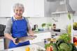 Frau bereitet Fisch in der Küche zu - Seniorin mit Hecht