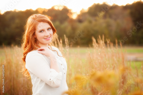 red haired girl in a field Poster
