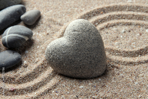 Foto op Plexiglas Stenen in het Zand Grey zen stone in shape of heart, on sand background