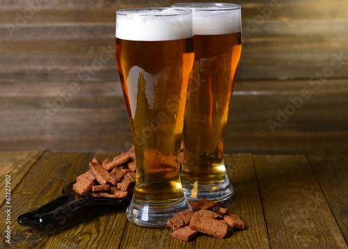 Canvas Prints Beer / Cider Glasses of beer with snack on table on wooden background