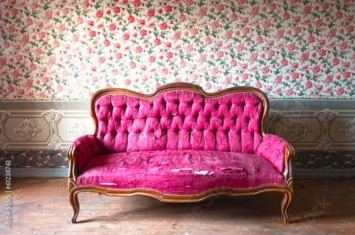 Fotografía  Old damaged red couch in an antique house. Flowers wallpaper