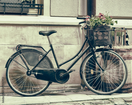 Poster Fiets Vintage stylized photo of Old bicycle carrying flowers