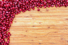 Border Of Pomegranate Seed On A Wood Background