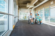 Medical Team Pushing Patients On Wheelchairs At Hospital Corrido