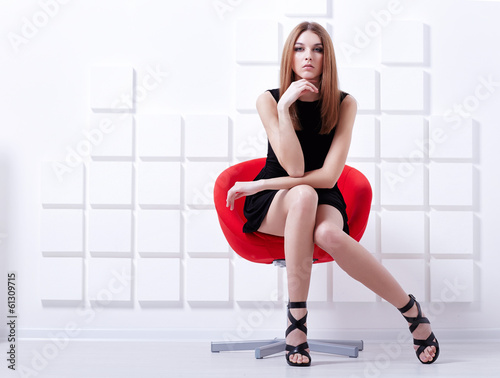 Sexy woman sitting on a chair. Fashion shot Wall mural