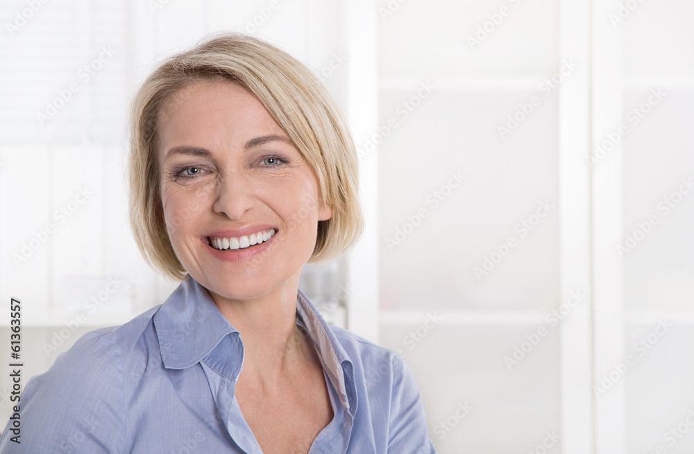 Fototapeta Ältere schöne blonde Frau - Portrait mit Hintergrund weiß blau
